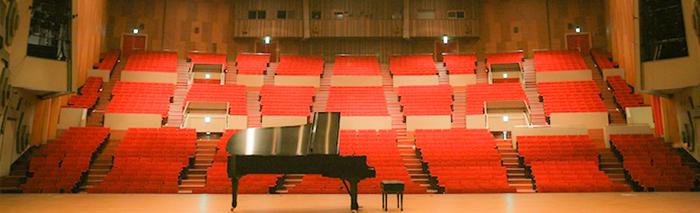 市民会館 大ホールで行われる イベント情報一覧を 下に表示しています イメージは 大ホールステージ上にピアノが設置されている 写真です